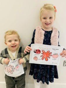 siblings holding red worksheet